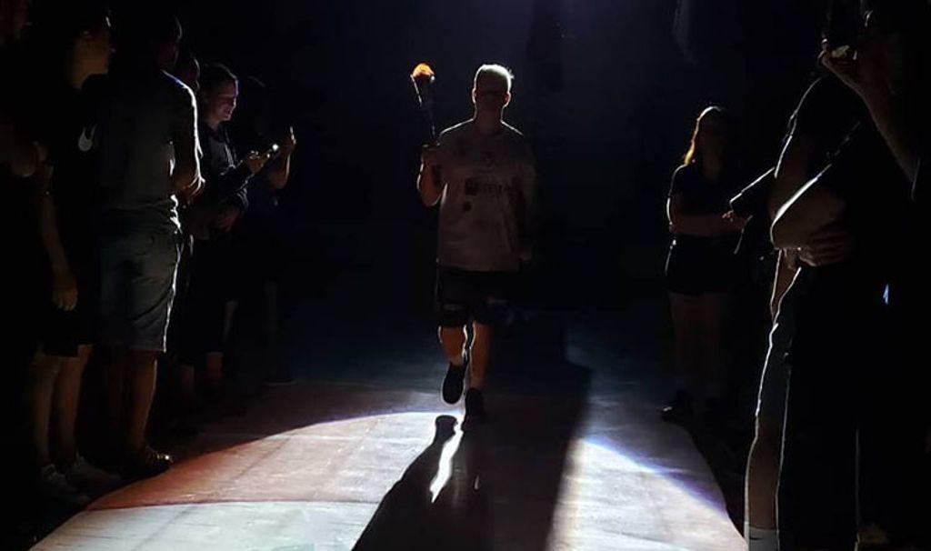 cadêmico carregando a chama olímpica dos Jogos Interfases