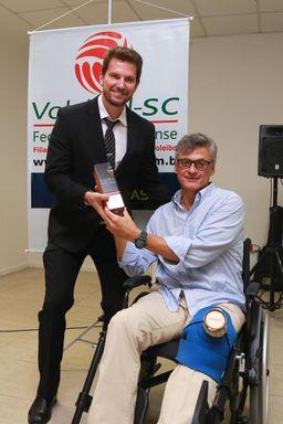 João Luchese recebendo o prêmio das mãos do técnico da Seleção Brasileira de Voleibol adulto masculino, Renan Dal Zotto