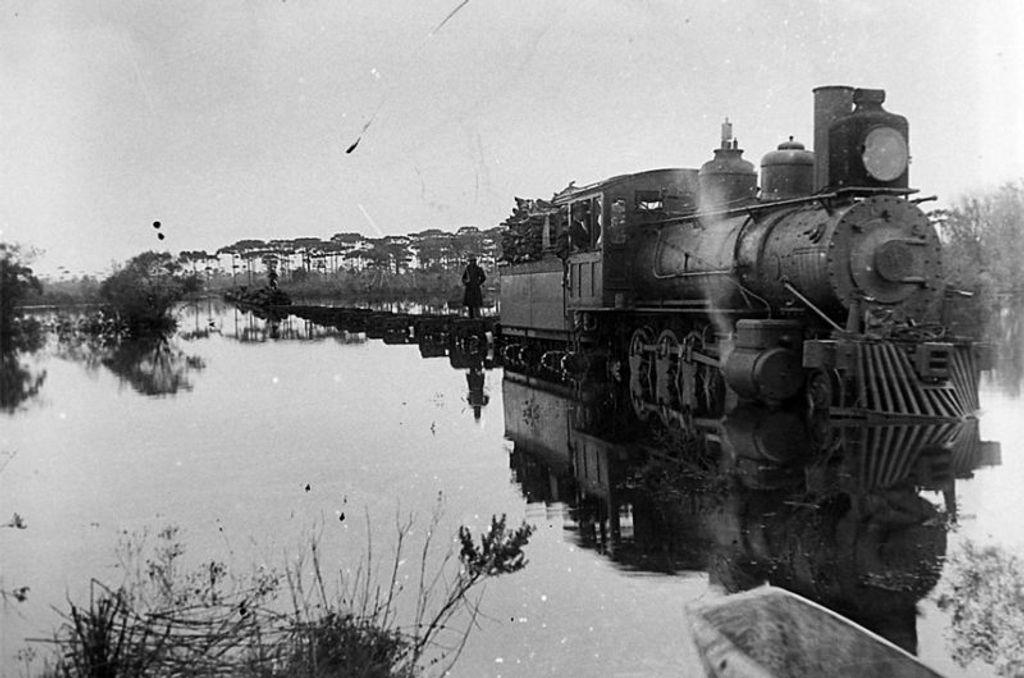 Foto histórica da Maria-Fumaça cortando trecho alagado da ferrovia.;