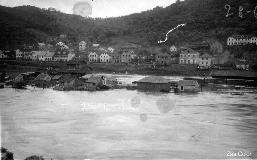 Casas e a estação ferroviária são atingidos pela enchente.