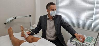 Dr. André Guerreiro aplicando o  exame de Ultrasonografia/Doppler