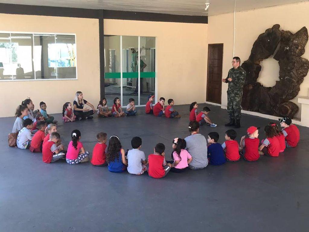 Crianças atentas à explicação do Policial